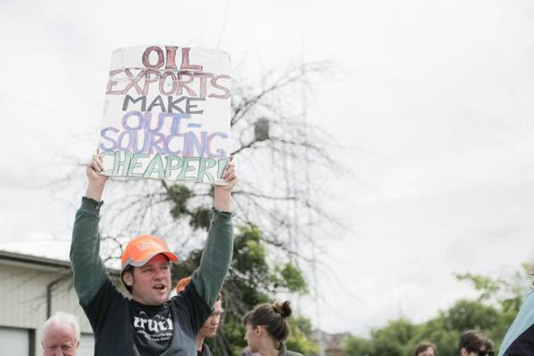 <p>A protester hoists a sign at a 2016 protest against oil trains in Vancouver, Washington.</p>