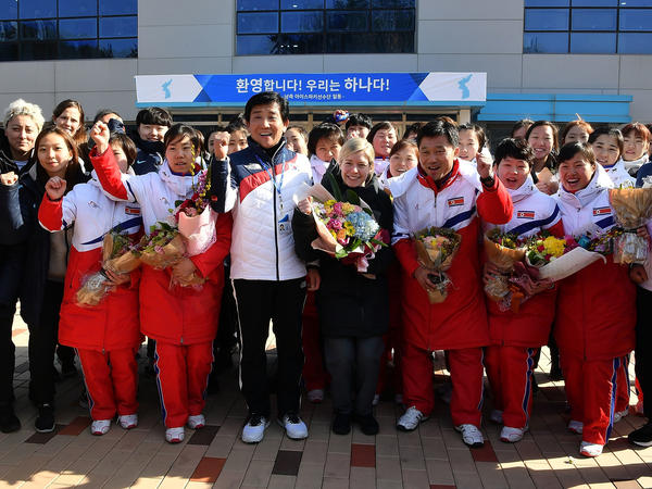 Sarah Murray, center, head coach of the unified Korean women's ice hockey team, says the team has come together since being formed through a political dialogue. Here, Murray and the South Korean players (in black) welcomed North Korea's coach Pak Chol-Ho and members of the northern team last month. The united team now wears all-white coats.