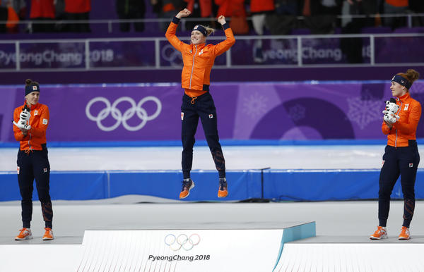 With a clean sweep for The Netherlands, gold medalist Carlijn Achtereekte jumps for joy as silver medalist Ireen Wust (left) and bronze medalist Antoinette de Jong watch after the women's 3,000-meter speedskating final at the 2018 Winter Olympics.