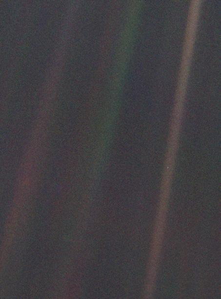 "This color image, known as the ""Pale Blue Dot,"" is part of the first-ever portrait of the solar system, which was taken by Voyager 1 in 1990. See that tiny dot caught in the middle of the rightmost beam? That's us: all of us."