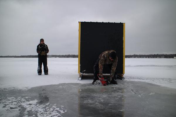 Ice fisherman preparing to fish for lake sturgeon on Black Lake in Michigan.
