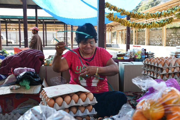 "Pansang Dema, 61, sits among her eggs and produce and praises the king for granting her 5 acres of land 19 years ago. A mother of seven, she's ""very happy"" that she can ""distribute all my land holdings to my children equally."""