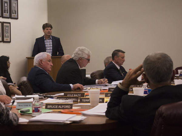 Members of the Arkansas State Plant Board listen to a presentation by Monsanto executive Ty Vaughn (standing) in September 2017.