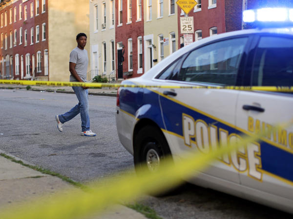 A man walks past a Baltimore police patrol car.