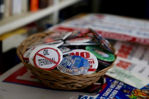 <p>A bowl of buttons sit on top a pile of campaign signs against various fossil fuel projects in the Pacific Northwest.</p>