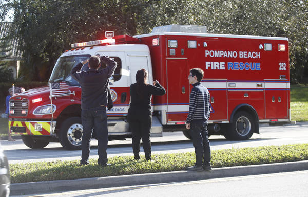 Family members watch a rescue vehicle pass by on Wednesday, in Parkland, Fla. A shooting at Marjory Stoneman Douglas High School school sent students rushing into the streets as SWAT team members swarmed in and locked down the building.