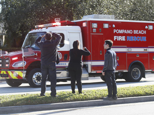Family members watch a rescue vehicle pass by on Wednesday, in Parkland, Fla. A shooting at Marjory Stoneman Douglas High School sent students rushing into the streets as SWAT team members swarmed in and locked down the building.
