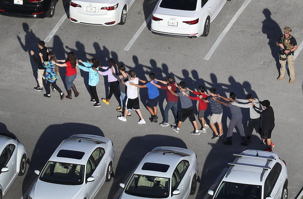People are brought out of Marjory Stoneman Douglas High School in Parkland, Fla., after a shooting at the school Wednesday. Officials say 17 people were killed and a suspect is in custody.