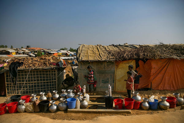 Kids wait for the water taps to be turned on in the Hakimpara camp.