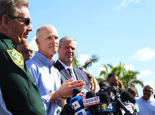 Broward Sheriff Scott Israel, left, watches Florida Gov. Rick Scott, center, speak at a press conference on Thursday.