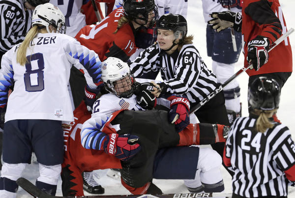 Official Jenni Heikkinen (No. 64) of Finland tries to separate women's hockey players Kelly Pannek (No. 12) of the United States and Laura Stacey (No. 7) of Canada as they scuffle.