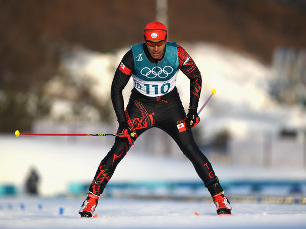 Pita Taufatofua of Tonga crosses the finish line during Friday's 15-kilometer cross-country ski competition. His goal, he'd said earlier, was to finish the race — and not hit a tree.
