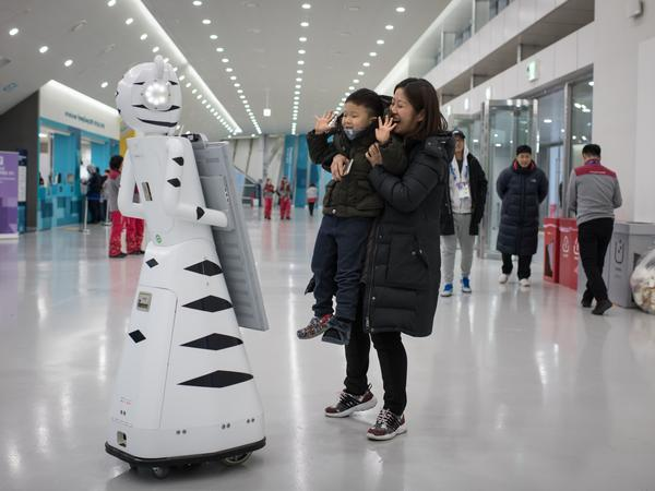 A woman and child pose for a photo before a robot before watching Switzerland and South Korea play ice hockey at the Winter Olympics on Saturday.