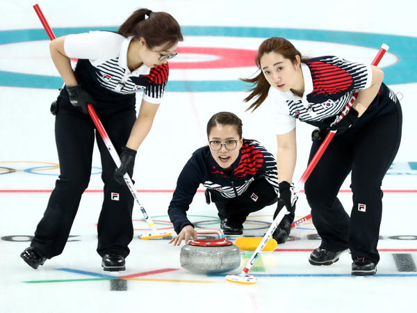 Eun Jung Kim delivers a stone between Yeong Mi Kim and Seon Yeong Kim during their competition against Switzerland on Friday.
