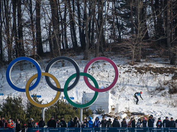 A cross-country skier passes Olympic rings on Feb. 16.