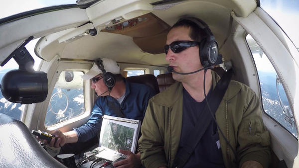<p>Jeff Lewis (left) listens for signals from below his airplane indicating the presence of fishers below in the Gifford Pinchot National Forest.</p>