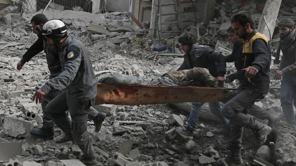 Members of the White Helmets, a Syrian civil defense group, rescue an injured civilian after a pro-regime airstrike Tuesday in eastern Ghouta.