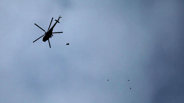 A Syrian attack helicopter made by Russia, an ally of President Bashar Assad, drops a payload Tuesday over the rebel-held eastern Ghouta on the outskirts of the capital, Damascus.