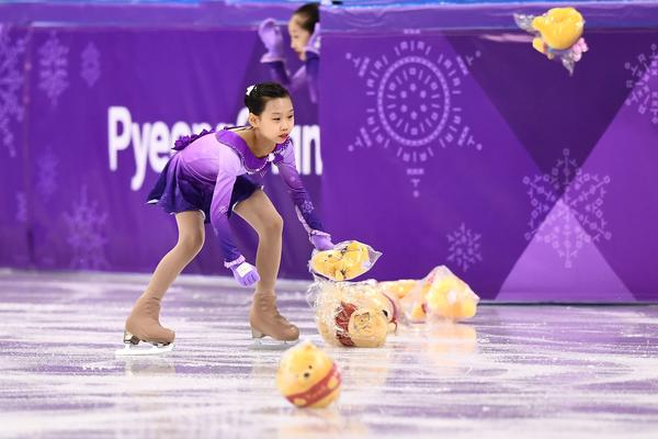"""A """"flower girl"""" collects Winnie the Pooh stuffed animals thrown by fans of Japanese gold medalist figure skater Yuzuru Hanyu on Feb. 16, during the men's figure skating short program."""