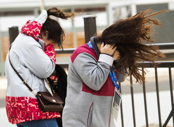 Olympic workers take cover from extreme wind gusts at the media village on Feb. 14. The wind disrupted events and schedules.