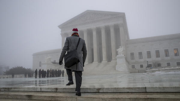 A man walks up in the fog at the U.S. Supreme Court to attend arguments last month. Justices issued multiple opinions on Wednesday.