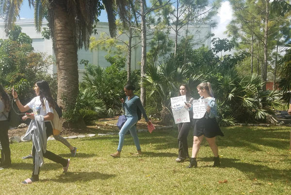 Miami Palmetto High students, walking out of the school building holding up handmade signs