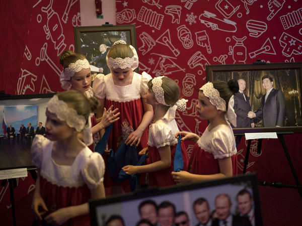 Russian girls stand next to photos of Russia's President Vladimir Putin during the opening of the Sports House, set up to support the Russian delegation of the 2018 Winter Olympics, in Gangneung on Feb. 9.