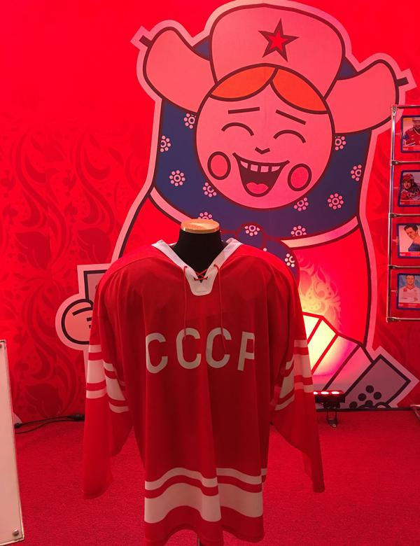 "A matryoshka doll and jersey bearing the Cyrillic letters for ""USSR"""