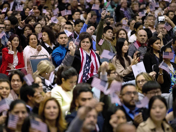 People wave U.S. flags during a 2017 naturalization ceremony at the Los Angeles Convention Center.