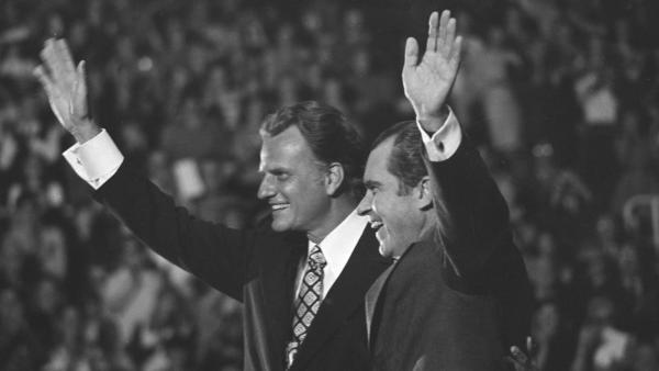 The late preacher Billy Graham, left, and President Richard Nixon wave to a crowd of 12,500 in 1971 in Charlotte, N.C., at an event honoring Graham.
