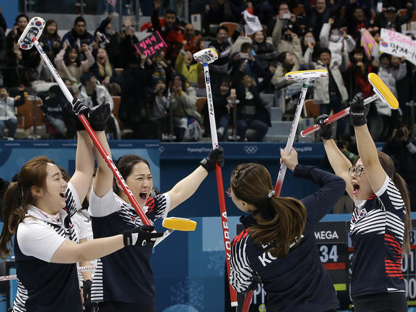Members of the South Korean women's curling team celebrate after their semifinal victory over Japan on Friday. The upset puts the team, which has become a sensation in the Olympic host country, into a gold medal round match-up with Sweden.