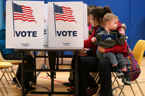 Karina Smith holds her 2-year-old son Kyler as she fills out her ballot last November in Alexandria, Va.