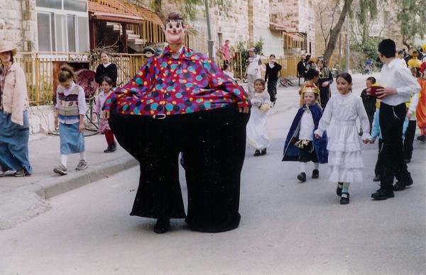 Children in costume carrying mishloach manot on the Purim holiday.