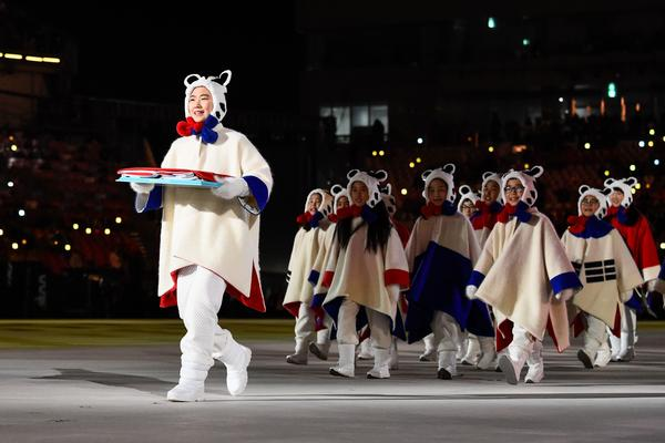 """Performers deliver a South Korean flag. Organizers had promised that the Olympic Stadium would be """"filled with the roar of compliments and the applause of friendship."""""""