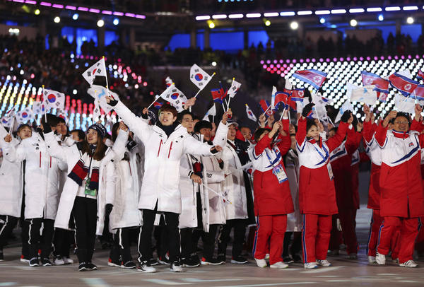 """North Koreans and South Koreans walk side by side. Thomas Bach, the head of the International Olympic Committee, said North and South Korea """"have shown how sport brings people together in our very fragile world."""""""
