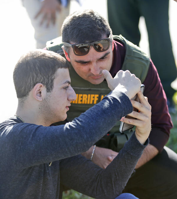 A student shows a law enforcement officer a photo or video from his phone, Wednesday, Feb. 14, 2018, in Parkland, Fla.
