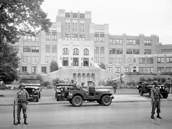 In this Sept. 26, 1957 photo, members of the 101st Airborne Division take up positions outside Central High School in Little Rock, Ark., after President Dwight D. Eisenhower ordered them into the city to enforce integration at the school.