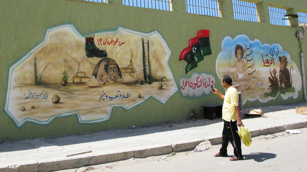 "A man takes a photo of an anti-Gadhafi mural in the Souk al-Joumah neighborhood of Tripoli, the Libyan capital. The former Libyan dictator often denounced the rebels who opposed him as ""rats."" Now, young artists delight in painting pictures depicting the missing Gadhafi as a rat in a hole. This mural shows Gadhafi as a rat, with his son Saif."