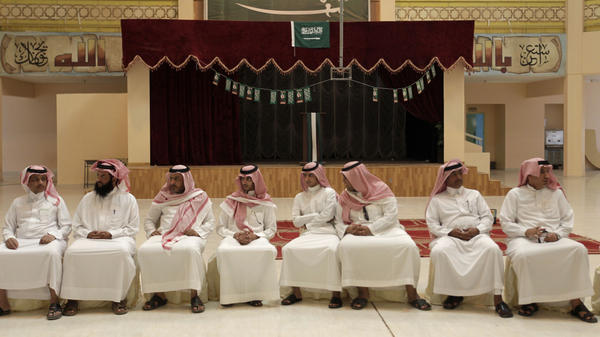 Saudi men wait to cast their votes in municipal elections in Riyadh, Saudi Arabia, on Thursday. Turnout appeared to be low. King Abdullah says that women will be allowed to vote in the next municipal elections, in 2015.