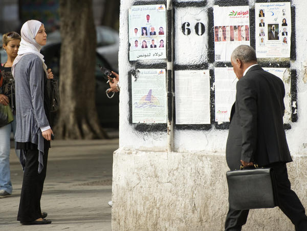 <p>A Tunisian woman in Tunis looks at posters presenting political candidates, on Oct. 20. Some Tunisians fear that if popular Islamist parties take power, they will seek to put their stamp on this moderate, secular state.</p>