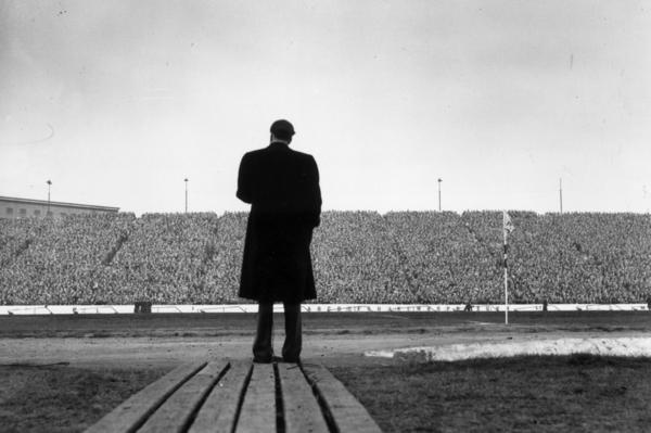 Graham's meetings often blended biblical lessons and old-time religion with entertainment. Here, Graham addresses the crowd during halftime at a match between Chelsea and Newcastle United in Stamford Bridge, London, in 1954.
