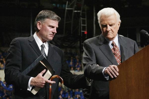 In 1995, with his health failing, Graham turned over the reins of the Billy Graham Evangelistic Association to his son, Franklin Graham. Here, Franklin assists his father at a rally on June 13, 2003, in Oklahoma City, Okla.