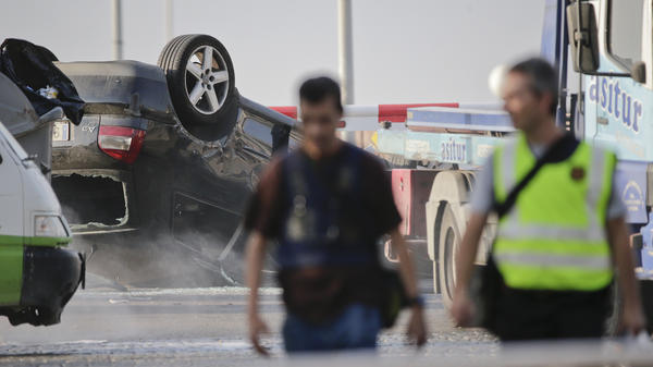 Police officers walk near an overturned car in Cambrils on Friday.