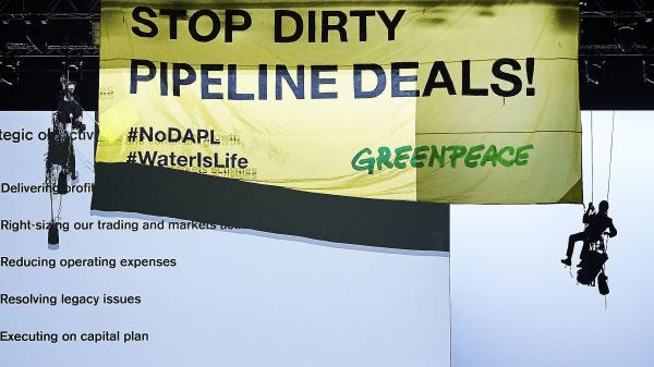 "Greenpeace activists hang a banner from the rafters at a bank shareholders' meeting earlier this year in Zurich, calling for it to ""STOP DIRTY PIPELINE DEALS!"" Also on the banner are hashtags supporting Dakota Access Pipeline protesters."