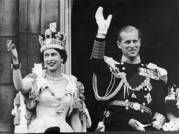 Queen Elizabeth II and the Duke of Edinburgh wave at the crowds from the balcony at Buckingham Palace on June 2, 1953.