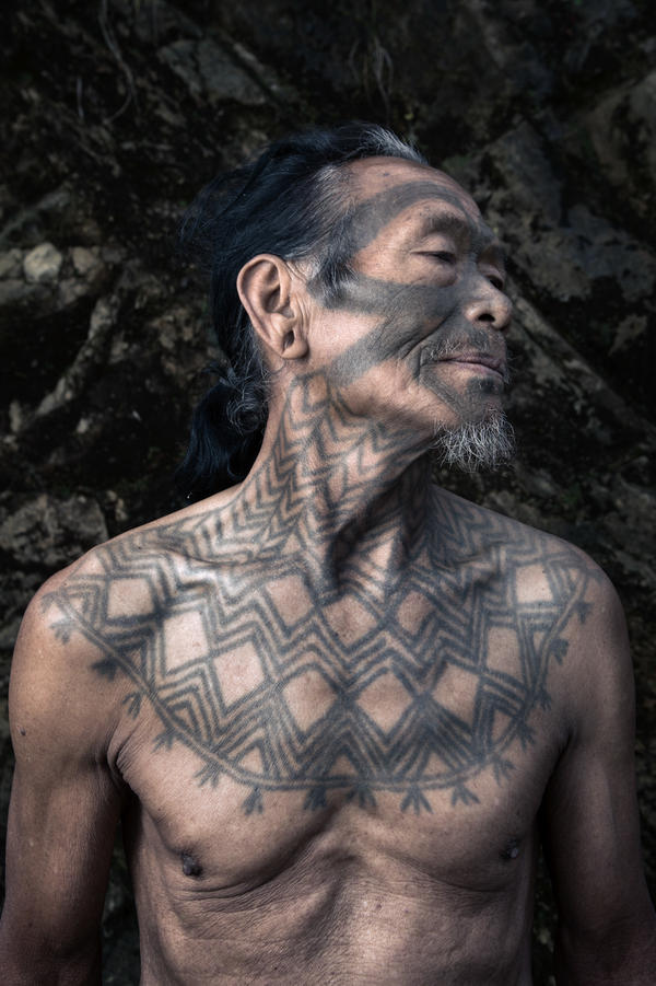 Chingham Chatrahpa, 75, shows off his facial and neck tattoos. A face tattoo would be etched after a man's first headhunting expedition, usually at the age of 18-to-25 years. Only a warrior who decapitated an enemy could get a neck tattoo.