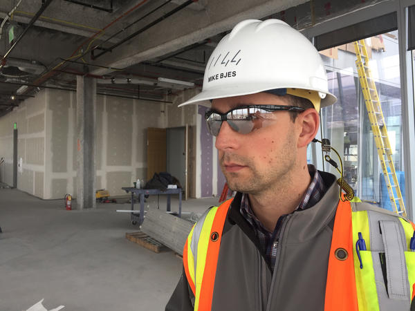 Construction manager Michael Bjes says this building's all-glass exterior has a protective coating, and an internal layer of argon gas, to reduce heat transfer and the use of air conditioning.