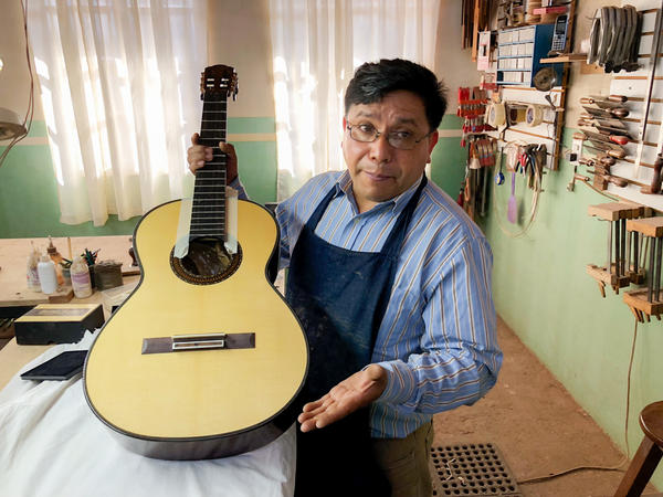 Master guitar maker Arnulfo Rubio Orozco holds up his latest project. It's taken him a month to craft this guitar with pearl accents and wood from southern Mexico.