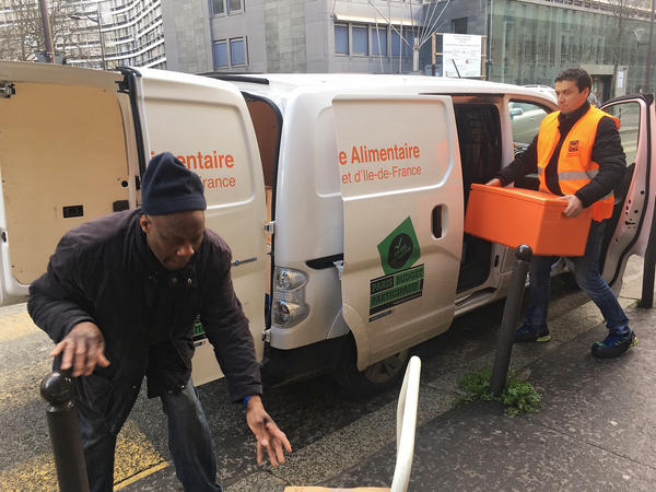 """Ahmed """"Doudou"""" Djerbrani, in the orange vest, delivers the food French supermarkets must donate to food banks by law."""