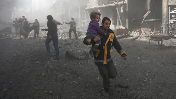 A Syrian man carries a child injured in the government bombing of eastern Ghouta, on the outskirts of Damascus on Monday.